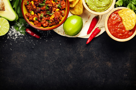 Mexican food concept: tortilla chips, guacamole, salsa, chilli with beans and fresh ingredients over vintage rusty metal background. Top view Stockfoto