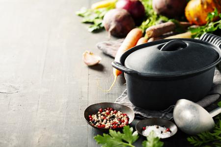 Gietijzeren pot en groenten op houten rustieke tafel. Zelfgemaakt eten, koken, vegetarisch concept Stockfoto