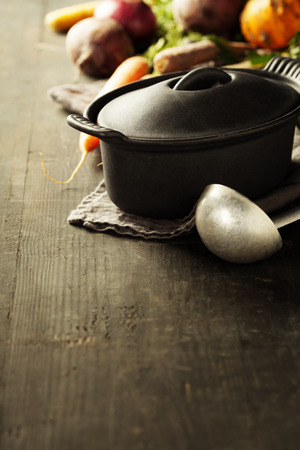 vegetarian food: Cast iron pot and vegetables on wooden rustic table. Homemade food, cooking, vegetarian concept