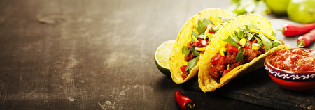 Mexican tacos with meat, beans and salsa on rustic background Imagens