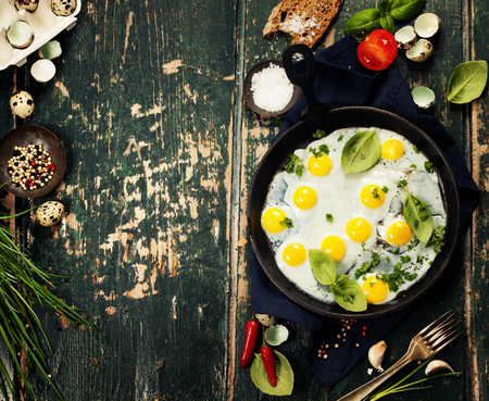 huevos de codorniz: Pan of fried eggs on old green background, top view