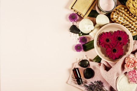 Spa background with sea salt, bowl ,flowers, water, soap bar, candles, essential oils, massage brush and flowers,top view. Flat lay. Pink background