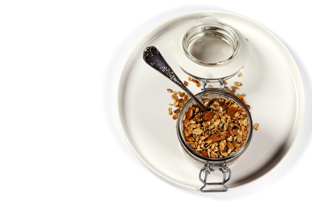 Homemade oatmeal granola with fruits and nuts in a glass jar on white background Stock Photo