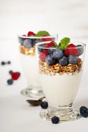 Freshly prepared yogurt parfait with fresh fruit and mint on white background