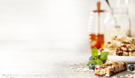 灰色の素朴なテーブル上にグラノーラ バー。健康的なスナック