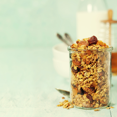sunflower seeds: Homemade granola on rustic table. Healthy breakfast of oatmeal, muesli, nuts, seeds and dried fruit.