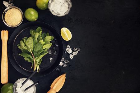 Mojito-cocktailingrediënten (verse munt, kalk, ijs) op rustieke achtergrond Stockfoto - 78470019