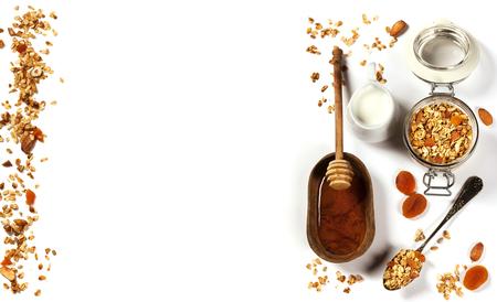 (ドライ フルーツとナッツ) 自家製グラノーラや健康的な朝食食材 - 蜂蜜、ミルク、白い背景の上の果実 写真素材