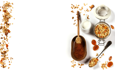 Homemade granola (with dried fruit and nuts) and healthy breakfast ingredients - honey, milk and fruits on white background Archivio Fotografico
