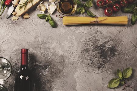 Italian food background with ravioli, vine tomatoes, basil, spaghetti, spinach, onion, parmesan, olive oil, garlic, peppercorns, rosemary and wine. Slate background