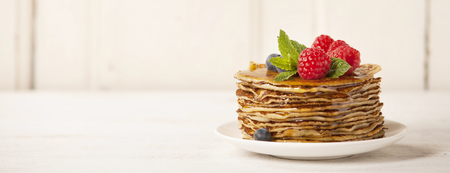 Stack of pancakes topped with berries and honey