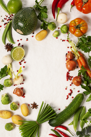 Frame of organic vegetables on white. Top view