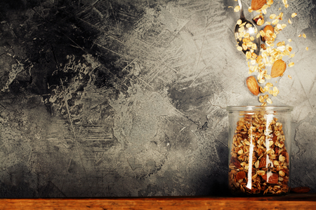 Flying breakfast against grey wall. Granola and spoon falling or flying in motion. Reklamní fotografie