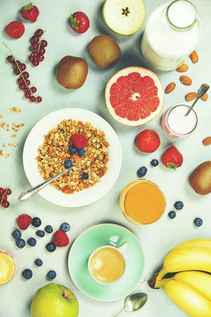 Healthy breakfast ingredients. Bowl of oat granola, almond milk, fresh fruits, berries, yogurt, juice and coffee. Top view