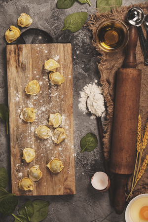 Top view on homemade pasta ravioli on old  table with ingredients and vintage kitchen accessories