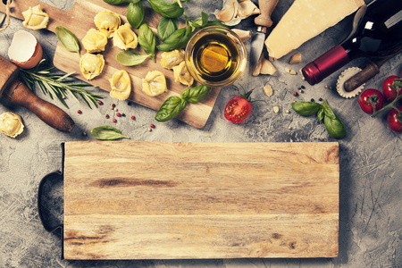 Italian food background with ravioli, vine tomatoes, basil, spaghetti, spinach, onion, parmesan, olive oil, garlic, peppercorns, rosemary and wine. Slate background Stock Photo - 81171229