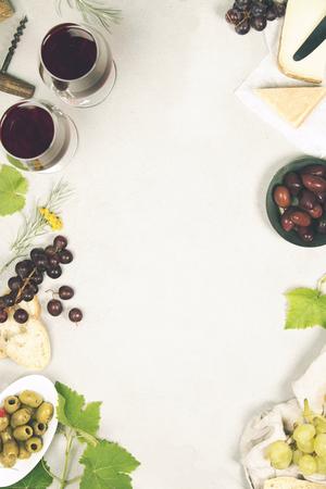Set de vinos y aperitivos. Variedad de queso, aceitunas, carne de prosciutto, rodajas de baguette, uvas negras y vasos de vino tinto sobre fondo de mármol gris, vista superior, espacio de copia Foto de archivo - 81366641