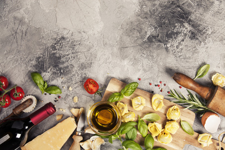 Italian food background with ravioli, vine tomatoes, basil, spaghetti, spinach, onion, parmesan, olive oil, garlic, peppercorns, rosemary and wine. Slate background Stock Photo - 81693613