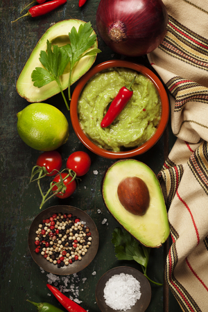 latinamerican: Bowl of Traditional latinamerican mexican sauce guacamole with fresh ingredients on dark rustic background. Top view