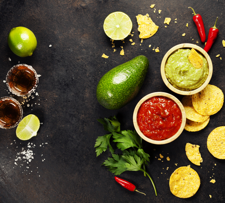 Mexican food concept: tortilla chips, guacamole, salsa, tequila shots and fresh ingredients over vintage rusty metal background. Top view