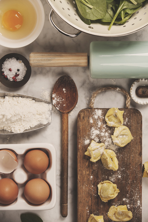 Top view on homemade pasta ravioli on old  table with ingredients and vintage kitchen accessories Stock Photo