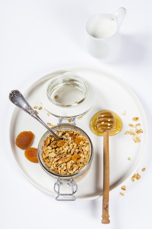 Homemade granola (with dried fruit and nuts) and healthy breakfast ingredients - honey, milk and fruits on white background Stock Photo