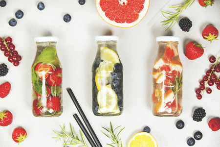 cold: Detox fruit infused flavored water. Refreshing summer homemade cocktail on grey background. Top view Stock Photo