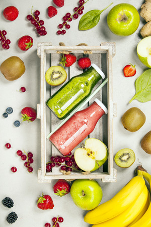 cold: Green and red fresh juices or smoothies with fruit, greens, vegetables on grey background, top view, selective focus. Detox, dieting, clean eating, vegetarian, vegan, fitness, healthy lifestyle concept
