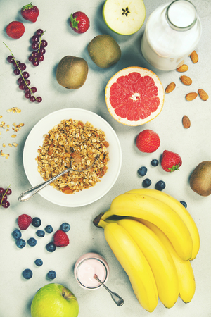 Healthy breakfast ingredients. Bowl of oat granola, almond milk, fresh fruits, berries, yogurt, juice and coffee. Top view