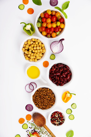 Selection of legumes spices herbs and organic vegetables. Ingredients for cooking. Food background on white. Top view copy space. Stock Photo