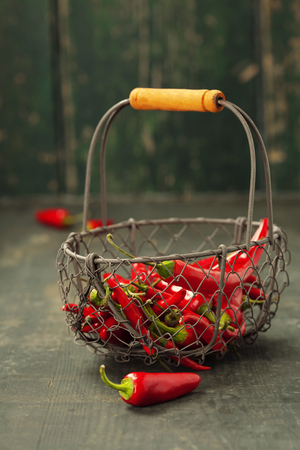Red hot chilli peppers in a metal basket on a wooden background