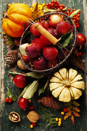 Apples in basket and autumn decorations on old wooden background