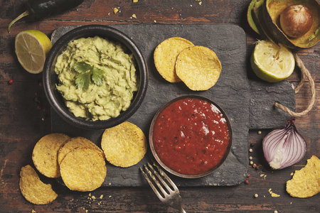 Mexican nachos chips with homemade fresh guacamole sauce and salsa over old background. Top view. Mexican food concept Stock Photo
