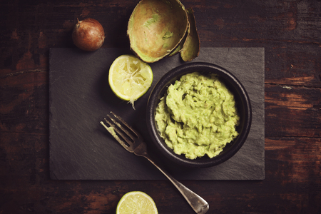 Homemade guacamole sauce on rustic background