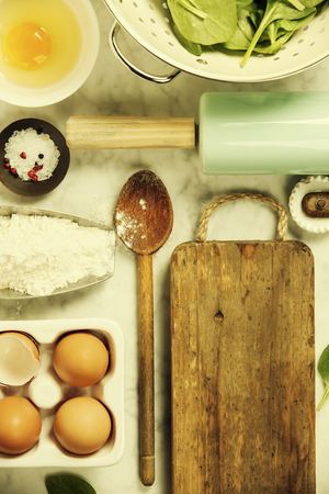 Top view on cooking ingredients and vintage kitchen accessories on old marble table Stock Photo