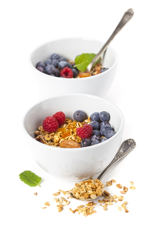 Healthy breakfast. Granola with fresh organic raspberries and blueberries on white background
