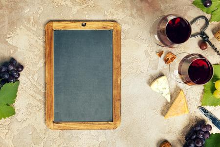 Bovenaanzicht van een lege krijtbord voor een wijnkaart of menu met wijn hapjes set: Franse kaas selectie, druiven en walnoten op rustieke achtergrond Stockfoto