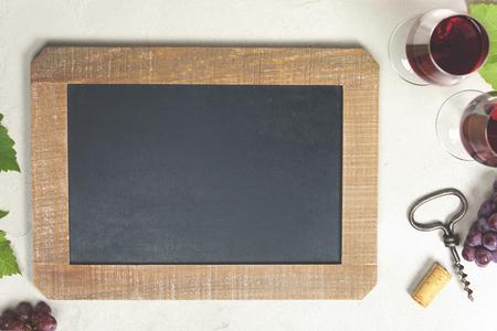 Hoogste mening van een leeg schoolbord voor een wijnlijst of menu met Wijn en druiven over grijze concrete achtergrond Stockfoto