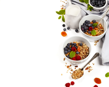 Homemade granola (with dried fruit and nuts) and healthy breakfast ingredients - honey, milk and berrieson white background Stock Photo - 90459600
