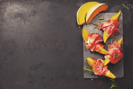 Prosciutto ham with cantaloupe melon, basil leaves and wine over dark grunge background. Top view, copy space Imagens