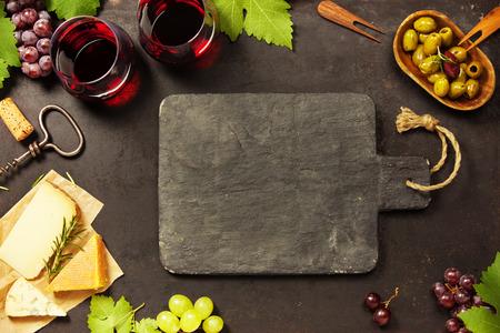 Wijn en snack set. Verscheidenheid van kaas, mediterrane olijven, zwarte en groene druiven en glazen rode wijn over donkere achtergrond, hoogste mening, exemplaarruimte