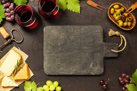 Wine and snack set. Variety of cheese, mediterranean olives, black and green grapes and glasses of red wine over dark background, top view, copy space Reklamní fotografie - 90736661