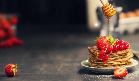 Ontbijt set. Zelfgemaakte pannenkoeken met verse bessen en honing op rustieke plaat over donkere houten tafel Stockfoto