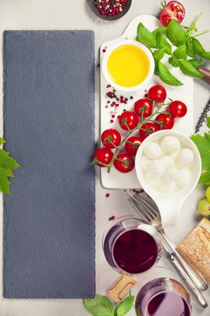 イタリアの前菜はワインをスナックします。モッツァレラチーズ、バジルの葉、トマト、オリーブ オイル、上面のコンクリート背景に赤ワインのグ