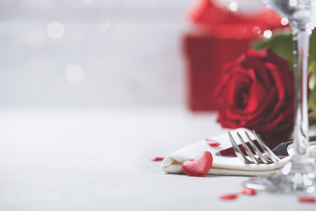 Valentines Day or Romantic dinner concept. Valentine day or proposal background. Close up view of restaurant table with romantic table place setting. Copy space