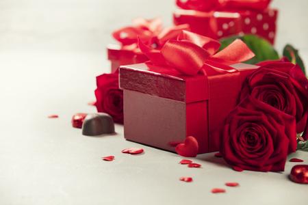 Valentinstag-Konzept. Geschenk mit roter Schleife auf dem hölzernen Hintergrund Valentinsgrußgeschenkbox gebunden mit einem roten Satinbandbogen auf rustikalem Hintergrund. Standard-Bild
