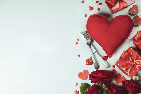 Valentines day background with fresh red roses, chocolate, fork, knife and gifts. Valentines day concept. Top view. Copy space.