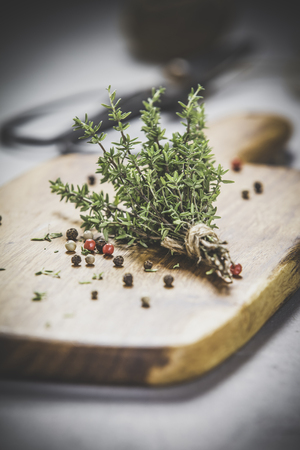bunch of thyme, spices and scissors on grey concrete background - Healthy food and cooking concept