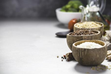 Variedade de arroz diferente em tigelas: baga de arroz, arroz integral e arroz de Risotto e ingredientes de cozimento em fundo cinza de concreto. Comer limpo Foto de archivo - 94142321