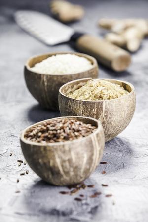 Variedade de arroz diferente em tigelas: Arroz de baga, arroz integral e arroz Risotto em fundo de pedra cinza. Foto de archivo - 94192034